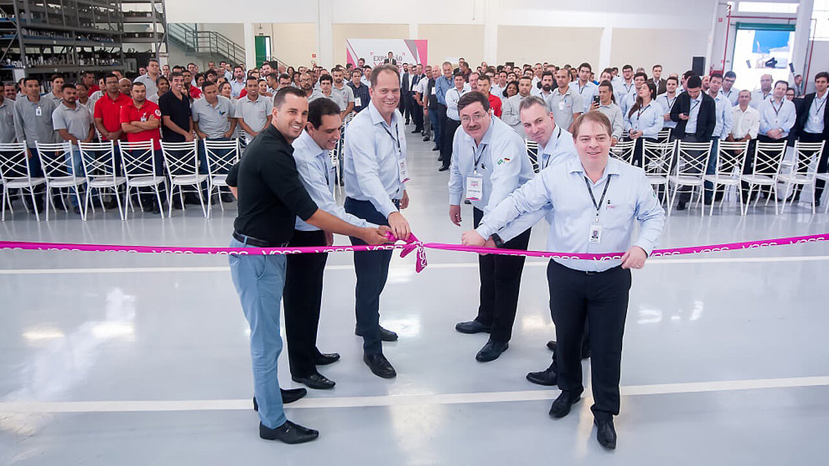 Six men are cutting a ribbon
